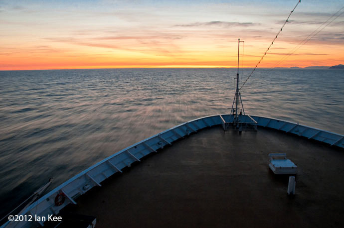 View over the bow of a ship, into the sunset