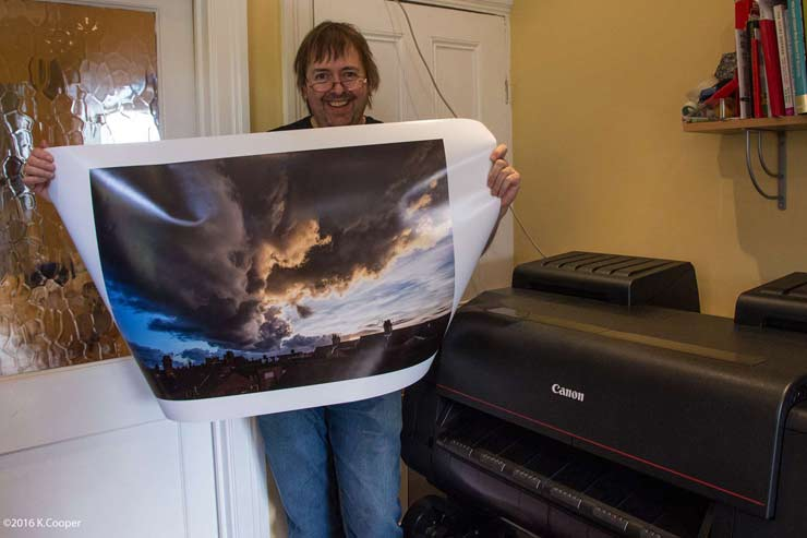 Keith Cooper with 20x30 print of a sunset over leicester