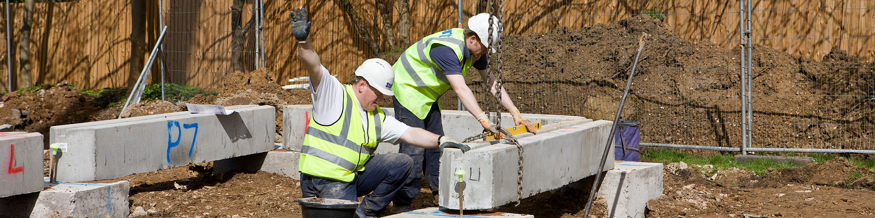 Two workers setting concrete lintel for house foundations